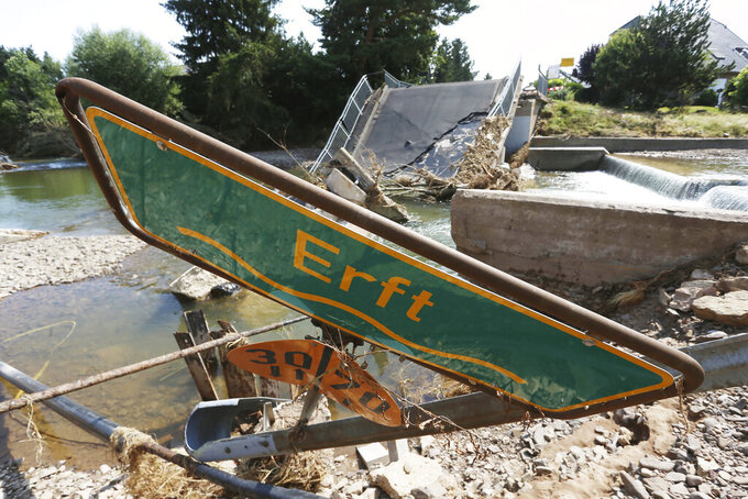 A location sign for the river Erft lies in the rubble in front of a destroyed bridge, in Stotzheim, Germany Thursday July 22, 2021. Heavy rains have caused devastating floods over much of the region, (David Young/dpa via AP)