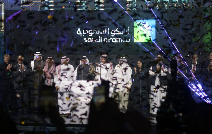 Saudi Arabia's state-owned oil company Saudi Armco and stock market officials celebrate during the official ceremony marking the debut of Aramco's initial public offering (IPO) on the Riyadh's stock market in Riyadh, Saudi Arabia, Wednesday, Dec. 11, 2019. (AP Photo/Amr Nabil)