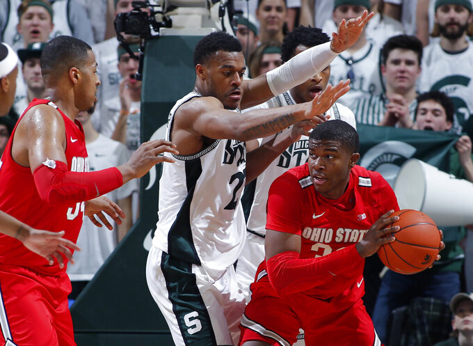 Ohio State's E.J. Liddell, right, maneuvers against Michigan State's Xavier Tillman, center, as Ohio State's Kaleb Wesson, left, watches during the first half of an NCAA college basketball game, Sunday, March 8, 2020, in East Lansing, Mich. (AP Photo/Al Goldis)