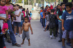 "In this Aug. 30, 2019, photo, migrants, many who were returned to Mexico under the Trump administration's ""Remain in Mexico"" program, wait in line to get a meal in an encampment near the Gateway International Bridge in Matamoros, Mexico. The program, officially called the Migrant Protection Protocols, was instituted by the U.S. and Mexico as a way of deterring migrants from crossing the border to seek asylum. (AP Photo/Veronica G. Cardenas)"