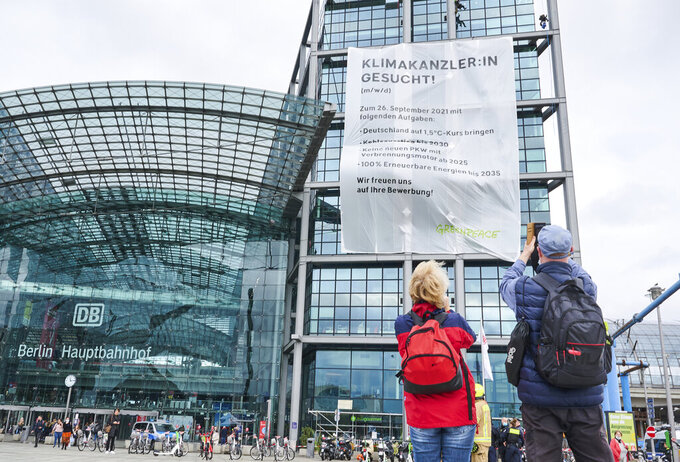 """Greenpeace activists hanging a large banner reading """"Climate Chancellor wanted!"""" at Berlin's main train station in Berlin, Germany, Friday, Sept. 17, 2021. German voters elect a new parliament on Sunday, Sept. 26, 2021. (Annette Riedl/dpa via AP)"""