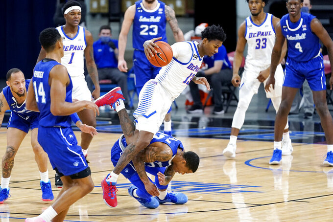 DePaul forward Darious Hall, left, tries to control the ball against Seton Hall guard Shavar Reynolds Jr., right, during the first half of an NCAA college basketball game in Chicago, Saturday, Jan. 9, 2021. (AP Photo/Nam Y. Huh)