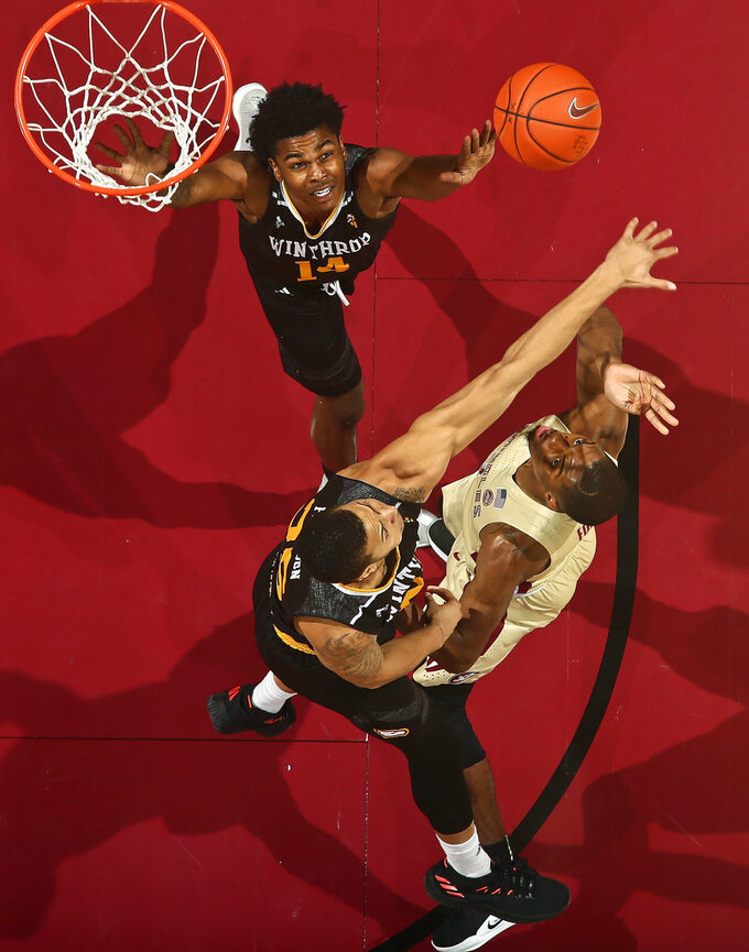 Florida State guard Trent Forrest (3) shoots as Winthrop forward Josh Ferguson (25) and guard Adam Pickett (14) defend in the first half of an NCAA college basketball game in Tallahassee, Fla., Tuesday, Jan. 1, 2019. Florida State won 87-76. (AP Photo/Phil Sears)
