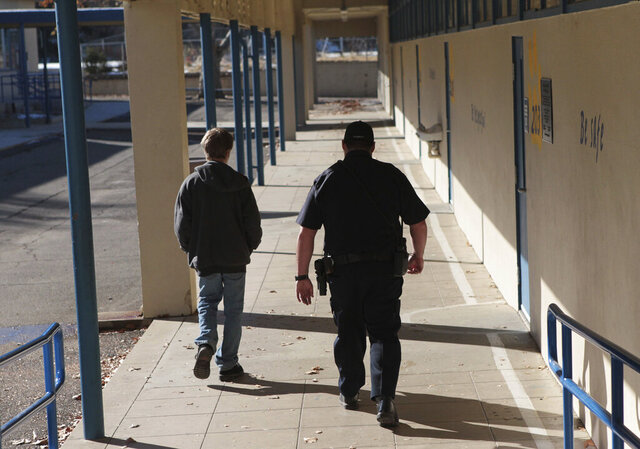 FILE - In this Dec. 9, 2013, file photo, a school resource officer in Anderson, Calif., walks a middle school student back to class. Portland Public Schools, Oregon's largest school district, will discontinue its use of Portland Police Bureau school resource officers. Superintendent Guadalupe Guerrero said Thursday, June 4, 2020, the district needed to