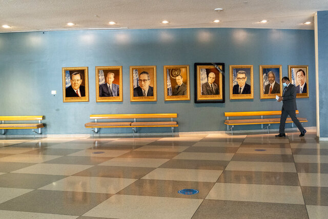 A man walk past portraits of former United Nations Secretary-Generals, Monday, Sept. 21, 2020 at United Nations headquarters. In 2020, which marks the 75th anniversary of the United Nations, the annual high-level meeting of world leaders around the U.N. General Assembly will be very different from years past because of the coronavirus pandemic. Leaders will not be traveling to the United Nations in New York for their addresses, which will be prerecorded. Most events related to the gathering will be held virtually. No access to world leaders on the U.N. grounds will be possible, therefore, and access to most anything will be extremely curtailed. (AP Photo/Mary Altaffer)