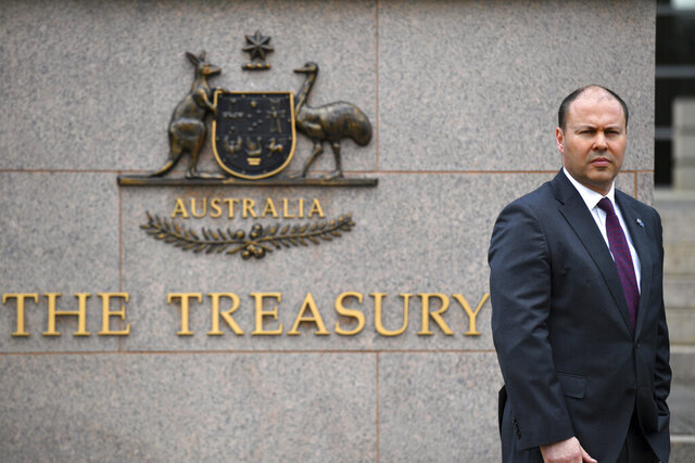 Australia's Treasurer Josh Frydenberg is photographed outside The Treasury in Canberra, Monday, Oct. 5, 2020. The Australian government will reveal a big spending financial blueprint for the next few years that will drive business investment and job creation while repairing pandemic damage to the economy. (Mick Tsikas/AAP Image via AP)
