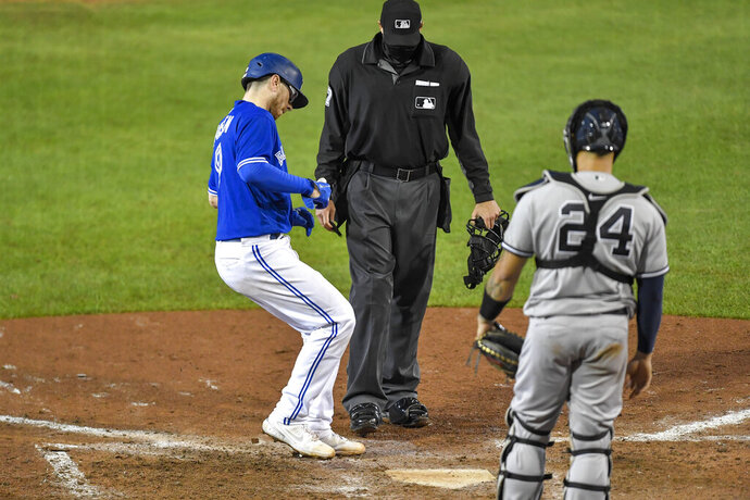 Toronto Blue Jays' Danny Jansen, left, crosses home plate in front of New York Yankees catcher Gary Sánchez, right, after hitting a solo home run during the eighth inning of a baseball game in Buffalo, N.Y., Wednesday, Sept. 23, 2020. (AP Photo/Adrian Kraus)