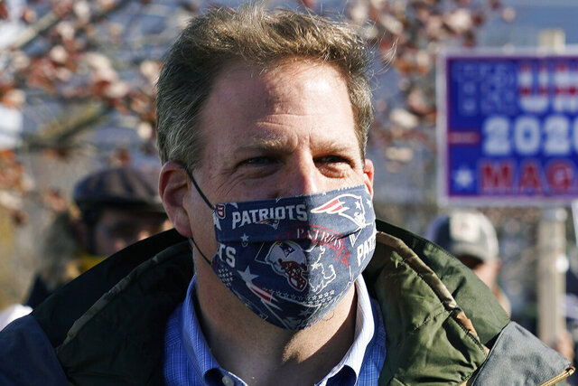 FILE - In this Nov. 3, 2020 file photograph, N.H. Gov. Chris Sununu wears a protective mask, due to the COVID-19 virus outbreak, at a polling station in Windham, N.H. New Hampshire joined three dozen other states, including the rest of New England, in enacting a statewide mask mandate as the coronavirus pandemic intensifies. Sununu issued an executive order requiring masks to be worn in public spaces, indoors or outside, when social distancing isn't possible, which goes into effect on Thursday Nov. 19, 2020. (AP Photo/Charles Krupa, File)