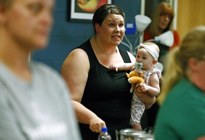In this Aug. 22, 2019 photo, Jessica Moloney, holding her 6-month-old daughter Amelia, expresses her displeasure at a meeting at Highland High School in Marengo, Ohio, about how the school board handled a recent incident where a child had access to a gun, pointed it at another student, and that parents weren't informed. Schools across the country have faced a backlash for favoring privacy over telling parents when there are threats in their children's classrooms. Safety experts advise schools to tell parents as much as they can as soon as they can about threats. (Fred Squillante/The Columbus Dispatch via AP)