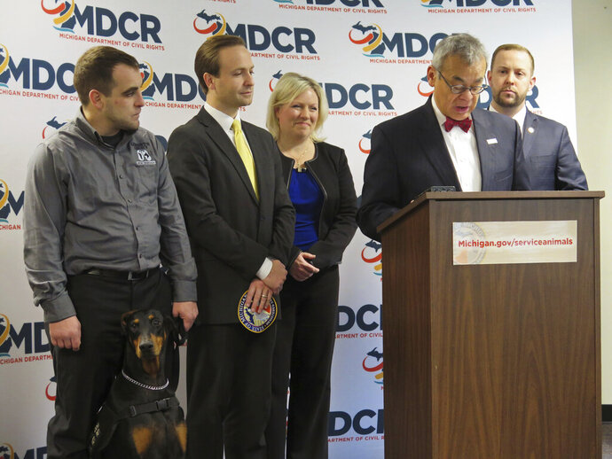 FILE - In this Wednesday, Jan. 13, 2016 file photo, Michigan Department of Civil Rights Director Agustin Arbulu, second right, speaks about a new service animal law in Lansing, Mich. Then Lt. Gov. Brian Calley, left, carries a patch that people with service animals will be able to obtain for free from the state to affix to their animal's vest. Michigan Gov. Gretchen Whitmer said Wednesday, Aug. 14, 2019, that Arbulu should resign or be fired after he made inappropriate, offensive comments about women. (AP Photo/David Eggert, File)