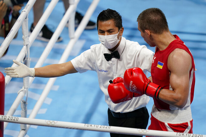 Ukraine's Oleksandr Khyzhniak, is red to his corner after being knocked down by Brazil's Hebert Sousa during their men's middleweight 75-kg boxing gold medal match at the 2020 Summer Olympics, Saturday, Aug. 7, 2021, in Tokyo, Japan. (AP Photo/Frank Franklin II)