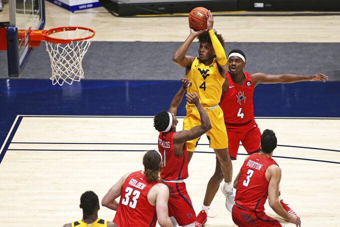 West Virginia guard Miles McBride (4) shoots while defended by Richmond guard Blake Francis (1) and forward Nathan Cayo (4) during the first half of an NCAA college basketball game Sunday, Dec. 13, 2020, in Morgantown, W.Va. (AP Photo/Kathleen Batten)