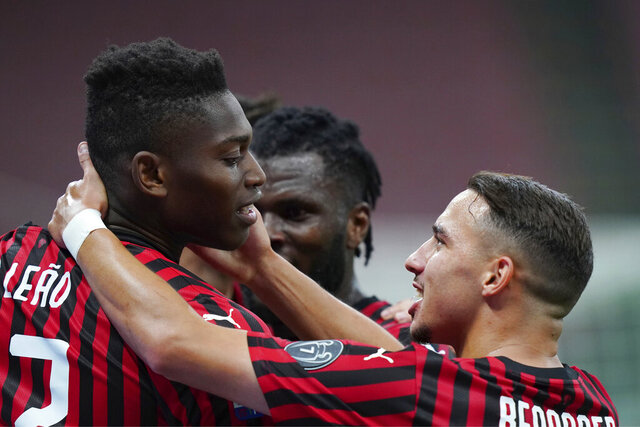 AC Milan's Rafael Leao, left, celebrates with his teammate Ismael Bennacer after scoring his side's 3rd goal during the Serie A soccer match between AC Milan and Juventus at the Milan San Siro Stadium, Italy, Tuesday, July 7, 2020. (Spada/LaPresse via AP)