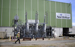 In this April 29, 2019 photo, a worker walks past the main transformer, no longer in service at Vermont Yankee Nuclear Power Station in Vernon, Vt. In January, privately held NorthStar Group Services completed the purchase of Vermont Yankee from New Orleans-based Entergy after federal and state regulators approved the sale of the reactor, closed since 2014. It marked the first permanent transfer of an operating license to a nuclear cleanup specialist for accelerated decommissioning. (AP Photo/Jessica Hill)