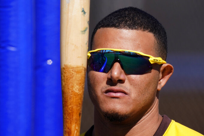 San Diego Padres' Manny Machado looks at his bat during spring training baseball practice Tuesday, Feb. 23, 2021, in Peoria, Ariz. (AP Photo/Charlie Riedel)