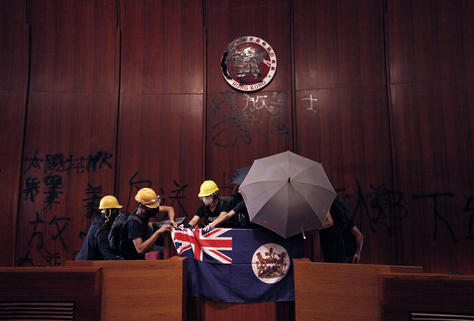 FILE - In this July 1, 2019, file photo, protesters put a Hong Kong colonial flag and deface the Hong Kong logo at the Legislative Chamber after they broke into the Legislative Council building in Hong Kong. Of all the dramatic photos showing hundreds of protesters storming Hong Kong's legislature this week, one image makes for particularly uncomfortable viewing in Beijing: The British colonial flag draped aloft a podium in the assembly's chamber. (AP Photo/Vincent Yu, File)