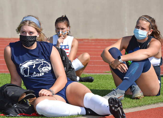 With face masks in place to slow the spread of COVID-19, Harbor Creek High School soccer players Haylee Wilson, 17, left, and Ali Tobin, 18, right, listen to Harbor Creek School District Superintendent Kelly Hess, not pictured, Monday, Aug. 24, 2020, at Paul J. Weitz stadium in Harborcreek Township, Erie County, Pennsylvania prior to the first day of official high school sports practices across the state. Athletes in Pennsylvania are allowed to remove face masks once they begin practicing or playing. (Christopher Millette/Erie Times-News via AP)