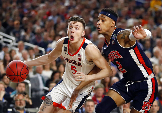 Virginia's Kyle Guy (5) drives against Auburn's Bryce Brown (2) during the first half in the semifinals of the Final Four NCAA college basketball tournament, Saturday, April 6, 2019, in Minneapolis. (AP Photo/Jeff Roberson)