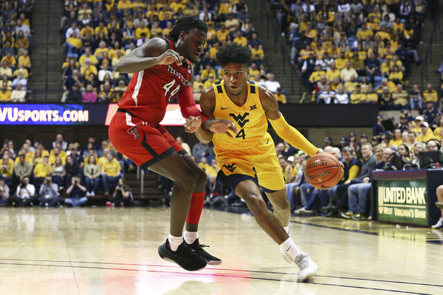 West Virginia guard Miles McBride (4) drives upcourt as he is defended by Texas Tech guard Chris Clarke (44) during the second half of an NCAA college basketball game Saturday, Jan. 11, 2020, in Morgantown, W.Va. (AP Photo/Kathleen Batten)