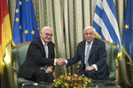 Greek President Prokopis Pavlopoulos, right, and his German counterpart Frank-Walter Steinmeier, shake hands after their meeting at the Presidential palace in Athens, on Wednesday, Oct. 11, 2018. Steinmeier is in Greece on a two-day official visit . (AP Photo/Petros Giannakouris)