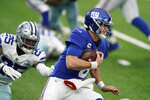 New York Giants quarterback Daniel Jones, right, runs from Dallas Cowboys' Xavier Woods during the first half of an NFL football game, Sunday, Jan. 3, 2021, in East Rutherford, N.J. (AP Photo/Corey Sipkin)