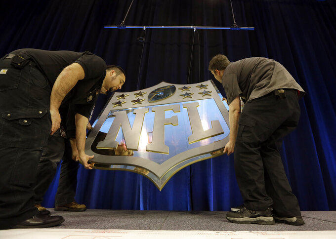 "FILE - In this Feb. 4, 2016, file photo, workers hang an NFL shield on the main stage before a news conference in San Francisco. The NFL and its players union have agreed to conduct ""virtual"" offseason workout programs until every team is permitted to open its facilities. Teams can hold classroom instruction, workouts and non-football educational programs using online platforms, according to a memo sent to the teams that was obtained by The Associated Press. (AP Photo/David J. Phillip, File)"