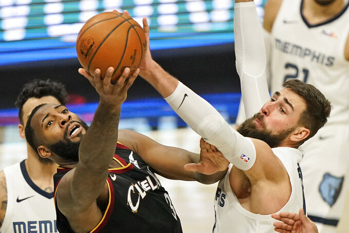 Cleveland Cavaliers' Andre Drummond, left, and Memphis Grizzlies' Jonas Valanciunas, right, battle for the ball in the second half of an NBA basketball game, Monday, Jan. 11, 2021, in Cleveland. (AP Photo/Tony Dejak)