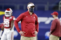 Oklahoma coach Lincoln Riley watches his team warm up before the Cotton Bowl NCAA college football game against Florida in Arlington, Texas, Wednesday, Dec. 30, 2020. (AP Photo/Michael Ainsworth)
