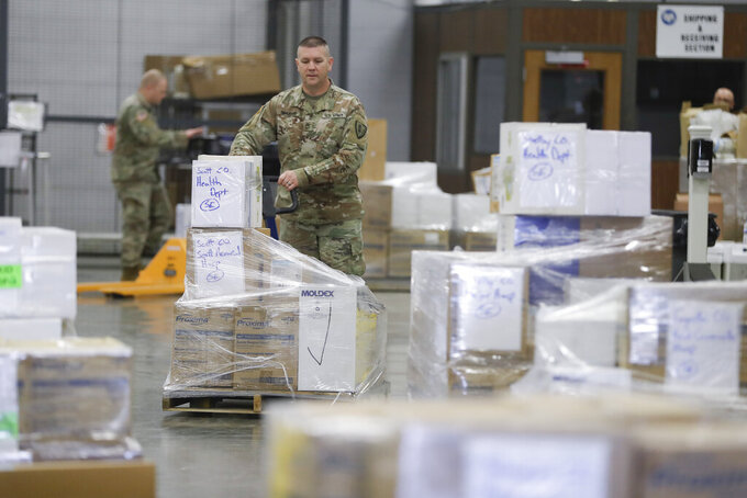 A Indiana National Guardsman lines up a pallets of medical supplies, Thursday, March 26, 2020, in Indianapolis. The medical supplies were being delivered to Indiana hospitals and health departments to help fight the coronavirus pandemic. (AP Photo/Darron Cummings)