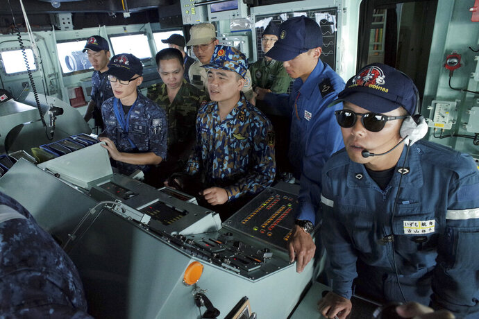 In this June 26, 2019, photo, Vietnam navy lieutenant Le Huu Hai, center, steers the wheel of Japan's Maritime Self-Defense Force helicopter carrier JS Izumo (DDH-183) during a ship maneuvering training session alongside Japanese officers off the coast of Brunei. The training is part of the Japan-ASEAN Ship Rider Cooperation Program, aimed at supporting defense cooperation and capacity building between Japan and ASEAN countries amid rising presence of the Chinese navy in South China Sea. (AP Photo/Emily Wang)