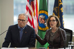 Oregon Gov. Kate Brown, right, with Washington Gov. Jay Inslee, talks to reporters before signing a memorandum of intent to replace the Interstate 5 bridge during an event in Vancouver, Wash., Monday, Nov. 18, 2019. (Nathan Howard/The Columbian via AP)