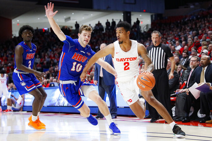 Dayton's Ibi Watson (2) drives past Houston Baptist's Ty Dalton (10) during the first half of an NCAA college basketball game, Tuesday, Dec. 3, 2019, in Dayton, Ohio. (AP Photo/John Minchillo)