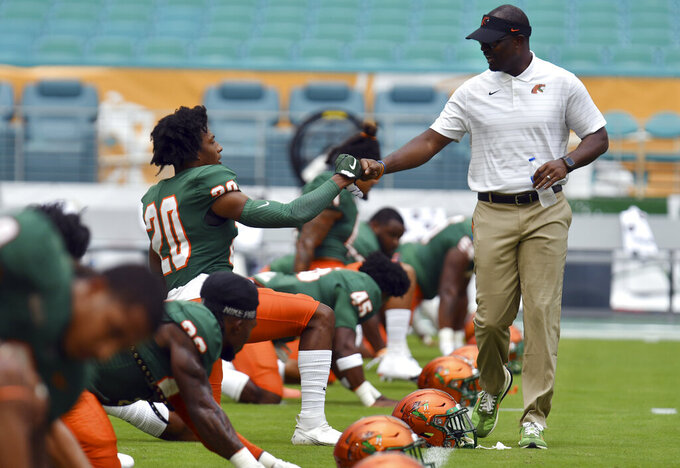 Florida A&M head coach Willie Simmons, right, greets defensive back Javan Morgan (20) during warmups before an NCAA college football game against Jackson State, Sunday, Sept. 5, 2021, in Miami Gardens, Fla. (AP Photo/Jim Rassol)