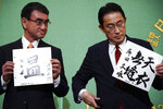 FILE - In this Sept. 18, 2021, file photo, Taro Kono, left, the cabinet minister in charge of vaccinations, and Fumio Kishida, former foreign minister, two of the four candidates for the presidential election of the ruling Liberal Democratic Party, pose with papers with their signs and words prior to a debate session hosted by the Japan National Press Club in Tokyo. The stakes are high as Japanese governing party members vote Wednesday, Sept. 29, 2021 for the four candidates seeking to replace Yoshihide Suga as prime minister. The next leader must address a pandemic-battered economy, a newly empowered military operating in a dangerous neighborhood, crucial ties with an inward-focused ally, Washington, and tense security standoffs with an emboldened China and its ally North Korea. (AP Photo/Eugene Hoshiko, Pool)