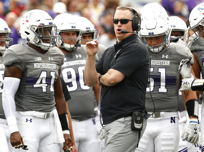 FILE - In this Sept. 8, 2018, file photo, Northwestern coach Pat Fitzgerald, center, speaks with his team during a break in the play in an NCAA college football game against Duke in Evanston, Ill. Northwestern will try not to make it back-to-back losses when they host Akron on Saturday, Sept. 15, 2018, after having their nine-game win streak last week. (AP Photo/Jim Young, File)