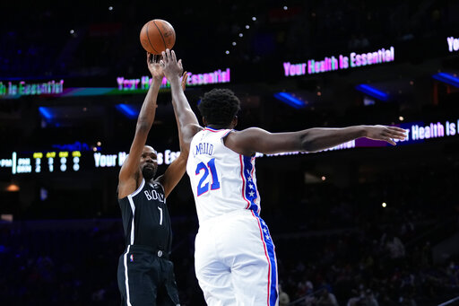 Brooklyn Nets' Kevin Durant, left, goes up for a shot against Philadelphia 76ers' Joel Embiid during the first half of a preseason NBA basketball game, Monday, Oct. 11, 2021, in Philadelphia. (AP Photo/Matt Slocum)