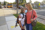 Aimee Burrows hugs her daughter Jovie after arriving at Whittier Elementary School on Tuesday, Aug. 24, 2021, in Salt Lake City. Kids in Salt Lake City are headed back to school Tuesday wearing masks after the mayor issued a mandate order despite heavy restrictions on mask mandates imposed by the GOP-dominated Legislature. (AP Photo/Rick Bowmer)