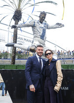 Former LA Galaxy MLS soccer midfielder David Beckham, left, and his wife Victoria pose with a statue of himself at Legends Plaza in front of Dignity Health Sports Park in Carson, Calif., Saturday, March 2, 2019. (AP Photo/Ringo H.W. Chiu)