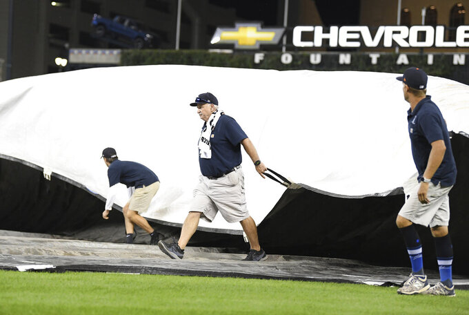 Members of the Detroit Tigers grounds crew cover the field with storms approaching after the sixth inning of the team's baseball game against the Milwaukee Brewers in Detroit, Tuesday, Sept. 14, 2021. (AP Photo/Lon Horwedel)