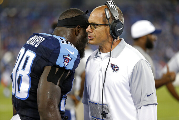 FILE - In this Aug. 23, 2015 file photo, Tennessee Titans linebackers coach Lou Spanos, right, talks with linebacker Brian Orakpo (98) in the first half of a preseason NFL football game against the St. Louis Rams in Nashville, Tenn. Spanos gets his first shot as a head coach after 26 years coaching in college and the NFL. Before becoming UConn's defensive coordinator in 2019, he served as an analyst for Nick Saban at Alabama. From 2014-18, he was linebackers coach for the Tennessee Titans and from 2012-13 he served as a defensive coordinator at UCLA.(AP Photo/Weston Kenney, File)