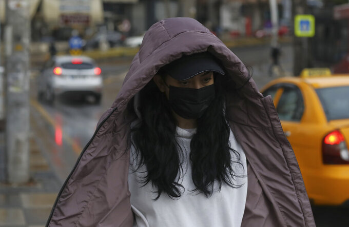 A woman wearing a mask to help protect against the spread of coronavirus, walk in the rain in Ankara, Turkey, Monday, March 29, 2021. Turkey is reinstating weekend lockdowns in most of Turkey's provinces and will also impose restrictions over the Muslim holy month of Ramadan following a sharp increase in COVID-19 cases.(AP Photo/Burhan Ozbilici)