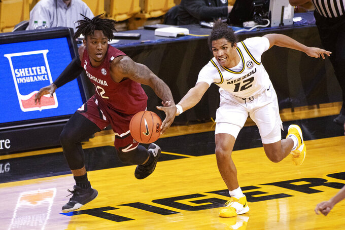 South Carolina's Trae Hannibal, left, and Missouri's Dru Smith, right, race for the ball during the first half of an NCAA college basketball game Tuesday, Jan. 19, 2021, in Columbia, Mo. (AP Photo/L.G. Patterson)