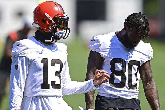 Cleveland Browns wide receiver Odell Beckham Jr. (13) talks with Jarvis Landry during an NFL football practice in Berea, Ohio, Tuesday, Aug. 24, 2021. (AP Photo/David Dermer)