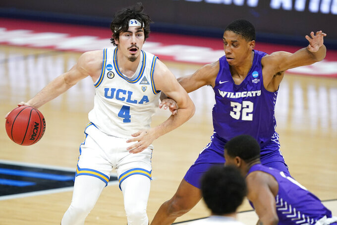UCLA's Jaime Jaquez Jr. (4) is defended by Abilene Christian's Joe Pleasant (32) during the first half of a college basketball game in the second round of the NCAA tournament at Bankers Life Fieldhouse in Indianapolis Monday, March 22, 2021. (AP Photo/Mark Humphrey)