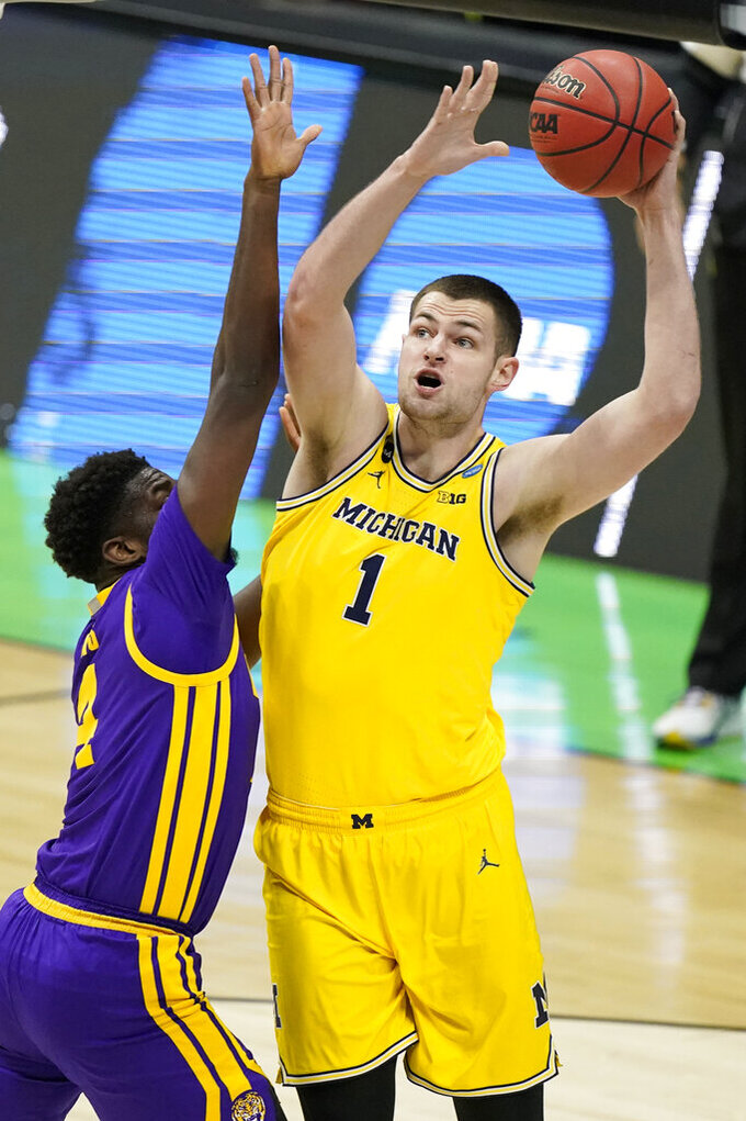 Michigan center Hunter Dickinson (1) shoots over LSU forward Darius Days (4) during the first half of a second-round game in the NCAA men's college basketball tournament at Lucas Oil Stadium Monday, March 22, 2021, in Indianapolis. (AP Photo/Darron Cummings)