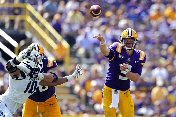 LSU quarterback Joe Burrow (9) passes under pressure from Utah State defensive end Tipa Galeai (10) in the first half of an NCAA college football game in Baton Rouge, La., Saturday, Oct. 5, 2019. (AP Photo/Gerald Herbert)
