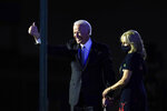 President-elect Joe Biden stands on stage with his wife Jill Biden as he gives the thumbs-up to the cheering crowd beyond the protective glass, Saturday, Nov. 7, 2020, in Wilmington, Del. (AP Photo/Carolyn Kaster)