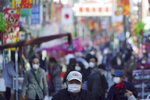 People wearing protective masks to help curb the spread of the coronavirus stroll along a shopping street in Tokyo Thursday, Jan. 14, 2021. The Japanese capital confirmed more than 1500 new coronavirus cases on Thursday. (AP Photo/Eugene Hoshiko)