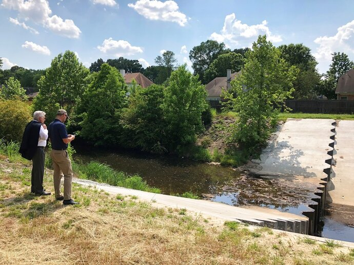 Two men inspect a U.S. Army Corps of Engineers project to prevent erosion in an important storm sewage channel in a Tennessee suburb, Tuesday, May 15, 2018, in Germantown, Tenn. (AP Photo/Adrian Sainz)