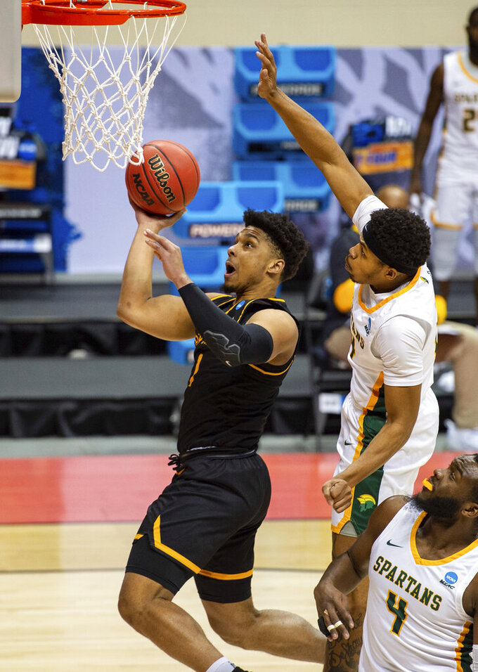 Appalachian State guard Justin Forrest (1) scores with a layup after getting past the defense of Norfolk State guard Devante Carter (14) during the first half of a First Four game in the NCAA men's college basketball tournament, Thursday, March 18, 2021, in Bloomington, Ind. (AP Photo/Doug McSchooler)